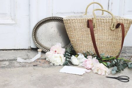 Feminine wedding still life composition with straw French basket bag, pink peonies flowers, eucalyptus, vintage silver tray with old scissors and silk ribbons. Old doors and grunge concrete floor. Stock fotó