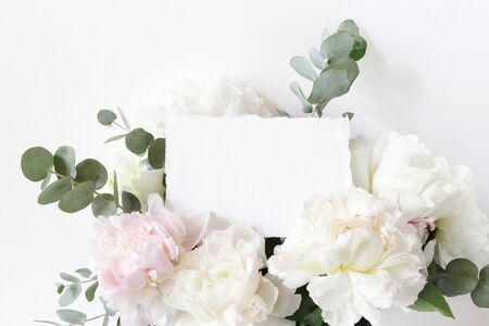 Feminine wedding, birthday mockup scene. Closeup of blank cotton paper card, invitation and floral bouquet. White and pink peonies flowers and eucalyptus. Styled stock photo.