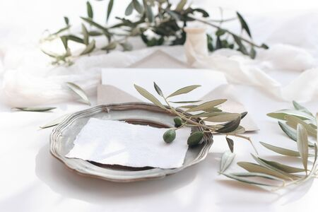 Summer wedding stationery mock-up scene. Blank greeting cards, invitations on vintage silver plate. Craft envelope, olive fruit, branch, silk ribbon and table runner. White background.