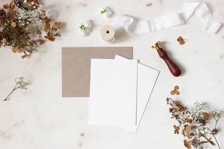 Winter, fall wedding, birthday table composition. Stationery mockup scene. Greeting cards, envelope, dry hydrangea flowers, wax seal stamp and ribbon on marble table backgound. Flat lay, top view.
