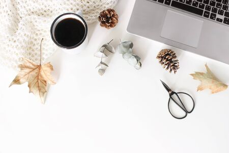 Autumn, fall workspace composition with open laptop. Cup of coffee, wool blanket, autumn leaves, dry eucalyptus, scissors and pine cones on white table background. Flat lay, top view. Blogger design.