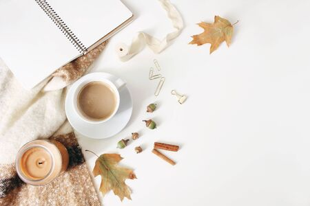 Autumn workspace still life, fall feminine scene. Notebook mock-up scene with cup of coffee, candle, cinnamon sticks, wool blanket, oak leaves and acorns. White table background. Flat lay, top view.