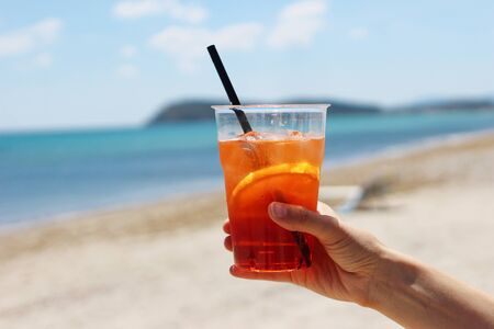 Closeup of womans hand holding chilled aperol coctail with orange slice, drinking straw and ice cubes. Italian alcoholic drink. Blurred background with sandy beach in sunny day, sea and blue sky Stock fotó