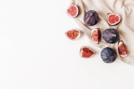 Decorative corner with fresh ripened purple figs and linen napkin. Creative composition of whole and sliced exotic fruit isolated on white table background. Flat lay, top view. Food photopfraphy.