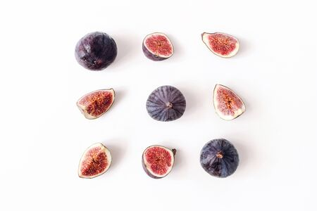 Fresh ripened purple figs. Creative square composition of the whole and sliced exotic fruit and isolated on white table background. Decorative pattern. Flat lay, top view from above. Food photography.