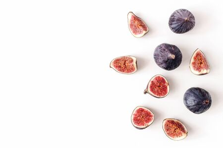 Fresh ripened purple figs. Creative composition, decorative banner of whole and sliced exotic fruit isolated on white table background. Natural pattern. Flat lay, top view. Food photography.