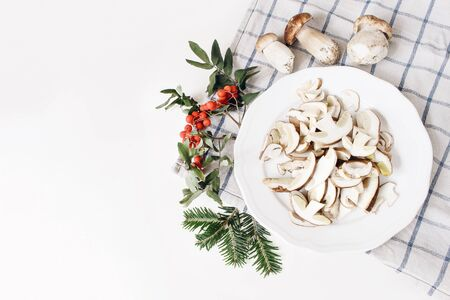 Autumn food arrangement. Composition of whole and sliced porcino mushrooms, ceps on plate. Rowan berries, leaves, fir branches and checkered tea towel on white table background. Fall design, flat lay, top view Stock fotó