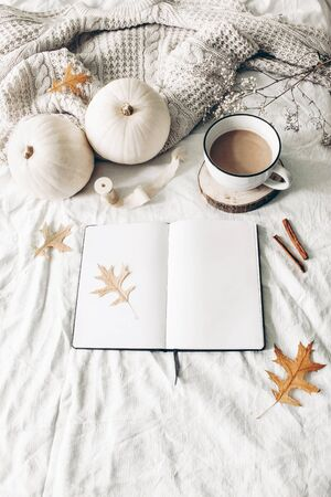 Autumn breakfast in bed composition. Blank open notebook mockup. Cup of coffee, white pumpkins, sweater, oak leaves and cinnamon on linen background. Thanksgiving, Halloween. Flat lay, top view Stock fotó