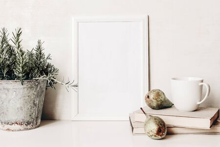White vertical blank wooden frame mockup. Composition of rosemary herb in old metal flower pot, books, cup of coffee and pears on white table. Home decor. Rustic summer poster product design. Stock fotó