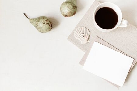 Feminine stationery, desktop mock-up scene. Blank greeting card, craft envelope, cup of coffee, sea shell, pears and old books. White table background. Flat lay, top view. Summer, fall composition.