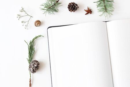 Christmas desktop stationery mock-up scene. Closeup of blank notebook. Frame of acorn, pine cones fir branches and gypsophila flowers on white table background. Flat lay, top view. Winter design.