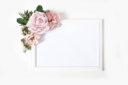 Wedding, birthday sign board mock-up scene. Blank white wooden frame. Decorative floral corner. Green leaves, pink peony, roses and wax flowers. White table background. Flat lay, top view.