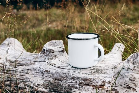 White metal mug sitting on old wood log. Blurred grass, meadow background. Outdoor tea, coffee time. Mockup of enamel cup. Lifestyle relax, trekking and camping concept.
