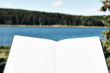 Close-up of blank notepad. Mock-up of empty book, diary. Blurred landscape with lake, forest and blue sky. Working and relaxing in nature. Summer vacation, outdoor travel concept. Stock fotó