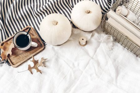 Autumn breakfast composition. Cup of coffee on wooden tray, white pumpkins, plaid, oak leaves and old books in golden basket. Linen background. Thanksgiving, Halloween. Flat lay, top view. Stock fotó