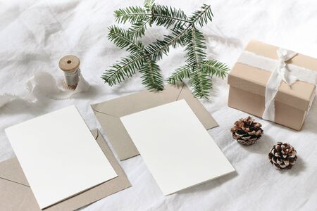 Christmas table, festive styled composition. Christmas greeting cards, envelopes mock-ups. Handmade gift box with silk ribbon, pine cones and fir tree branch on white linen background. Top view.