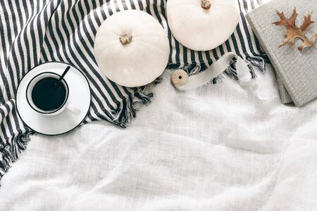 Autumn breakfast in bed composition. Cup of coffee, white pumpkins, plaid, oak leaves and old books. Linen background. Thanksgiving, Halloween holiday concept. Empty space. Flat lay, top view. Stock fotó
