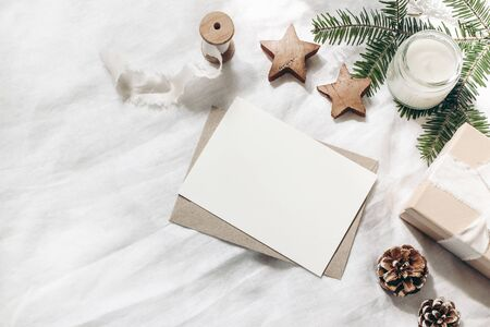 Christmas composition. Blank greeting card, envelope mock-up scene. Decorative corner. Pine cones, fir tree branches, gift box and wooden stars on white table, linen background. Flat lay, top view.
