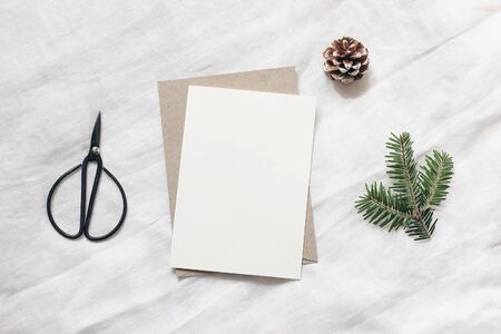 Christmas blank greeting card mock-up scene. Festive winter wedding composition. Envelope, pine cone, black vintage scissors and fir tree branch on white table, linen background. Flat lay, top view.
