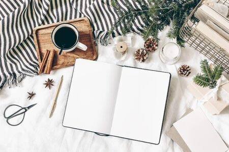 Christmas, winter composition. Blank greeting card, open diary, sketch book mock-up scene. Cup of coffee, old book, pine cones, fir branches, gift box and candle on white table, linen background. Flat lay, top view. Stock fotó
