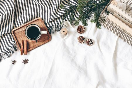 Christmas styled composition. Cup of coffee, plaid, old books in golden basket, pine cones, fir branches on white table, linen background. Flat lay, top view. Winter holiday lifestyle concept, web banner.