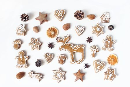 Decorative Christmas food pattern. Winter composition of gingerbread cookies, anise stars, pine cones and dry orange fruit slices isolated on white table background. Flat lay, top view. Stock fotó
