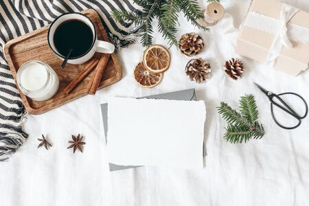 Christmas, winter composition. Blank greeting card mock-up scene. Cup of coffee, gift box, pine cones, fir branches, black scissors and candle on white table, linen background. Flat lay, top view.