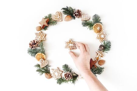 Christmas circle floral composition with womans hand holding cookie. Wreath of fir tree branches, pine cones, gingerbreads and dry orange slices on white background. Winter holiday design. Flat lay.