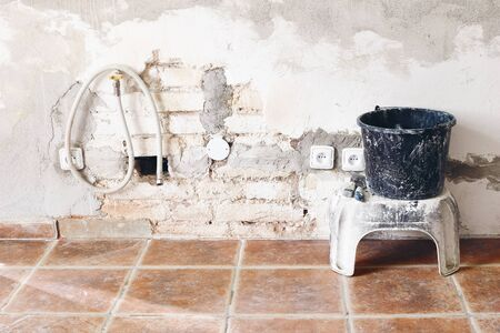 Black dirty bucket and spatula tools and white brick wall. Unfinished room reconstruction. Home repair, improvement. Work in progress. Rebuilding, renovation concept. Old apartment under construction.