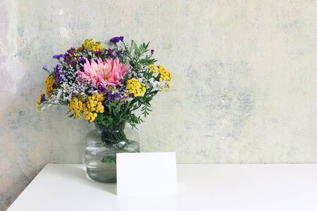 Glass vase with beautiful colorful bouquet of dahlia, tansies and aster flowers. Grunge old wall background. Feminine wedding, birthday mock-up scene with blank greeting card. Empty copy space.