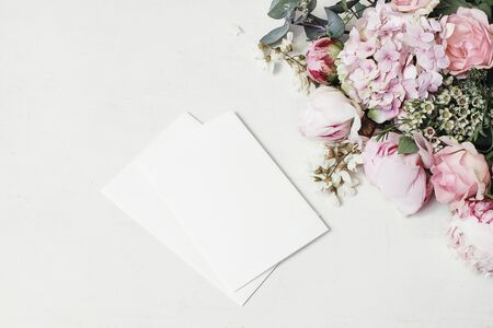 Feminine wedding, birthday mock-up scene. Decorative floral corner of peony, hydrangea, roses and locust flowers. Blank paper greeting cards on white wooden table background. Fat lay, top view