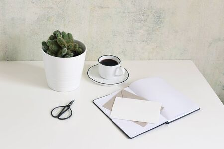 White office desk table mock-up scene with cup of coffee, cactus, open notebook, blank greeting card, envelope and scissors. Old grunge wall background, hipster workspace, lifestyle composition. Stock fotó