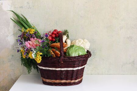 Fresh organic assorted vegetables and autumn garden flowers in handmade wicker basket. Farm still life composition. Harvest, gardening concept. Healthy food, eating scene, grunge wall background.