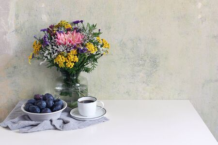Feminine wedding, birthday scene with cup of coffee and plum fruit bowl. Glass vase with beautiful colorful bouquet of dahlia, tansies and aster flowers on white table with linen cloth, grunge wall.