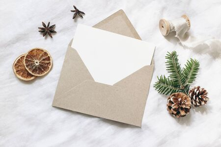 Christmas blank greeting card mock-up scene. Festive winter wedding composition. Craft envelope, pine cone, dry orange fruit slices and fir tree branch on white table, linen background, flat lay, top view.