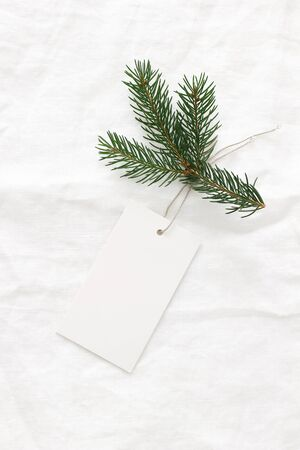Close-up of blank white paper gift tag with rope and green fir branch on white linen tablecloth background. Price tag nmock-up scene. Christmas composition, flat lay, top view, vertical.