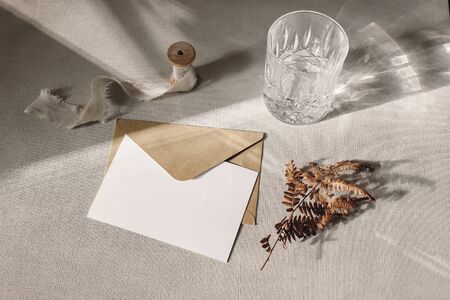 Autumn, fall stationery mockup scene. Blank greeting card, invitation, craft paper envelope, dry fern leaf and sparkling glass of water on grey table linen background in sunlight. Harsh shadow play. Banco de Imagens