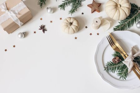 Traditional Christmas table place setting. Golden cutlery, porcelain plate, fir tree branches, gift box, pine cones and white pumkins. Christmas baubles decoration. Holidays background. Flat lay, top.
