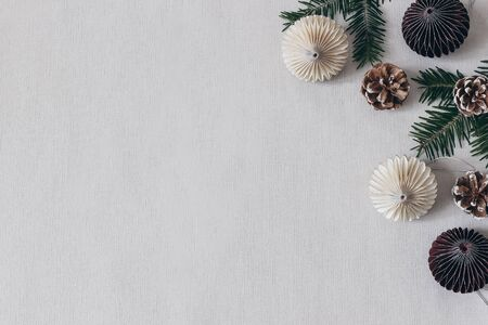 Christmas styled stock composition. Decorative paper Christmas ornaments, pine cones and fir tree branches on grey table linen background. Flat lay, top view. Winter festive pattern, empty copy space.
