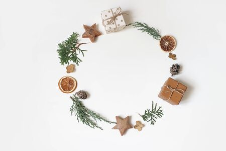 Christmas circle floral composition. Wreath of juniperus branches, pine cones, gift boxes, wooden stars and dry orange fruit on white background. Winter, advent design and decoration. Flat lay, top