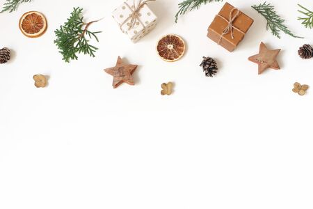 Christmas floral frame, web banner. Garland of juniperus, cypress branches, pine cones, gift boxes, wooden stars and dry orange fruit on white background. Winter design and decoration. Flat lay, top.