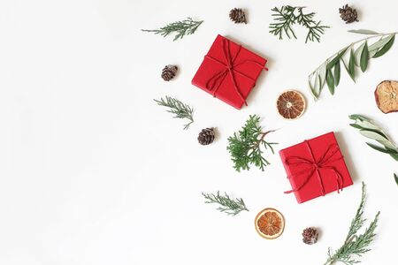 Christmas festive composition, pattern. Olive, cypress tree branches, pine cones, red gift boxes, dry apple, orange fruit on white background. Winter design and decoration. Flat lay, top view.