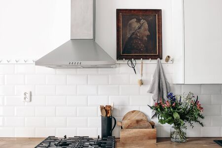 Modern eclectic kitchen interior. White brick wall with metro tiles, peg rails and oil painting. Wooden countertop, stainless steel hood and gas stove. Scandinavian design. Home staging, concept.
