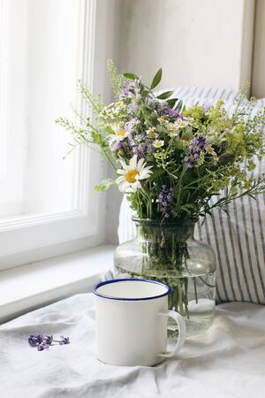 Summer still life scene. Enamel mug, wild flowers bouquet and linen cushion. Vintage feminine photo, rustic design. Floral composition with coffee, lavender, capsella and daisies. Table at window.