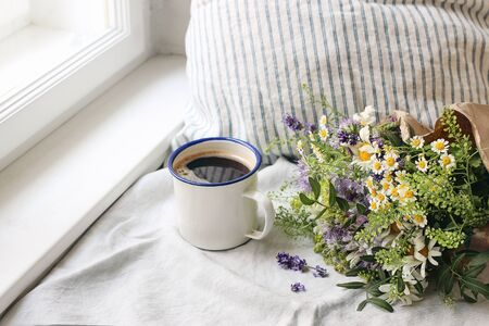 Summer breakfast scene. Enamel mug, wild flowers bouquet and linen cushion. Vintage feminine photo, rustic design, floral composition with coffee, lavender, capsella and daisies on table at window.