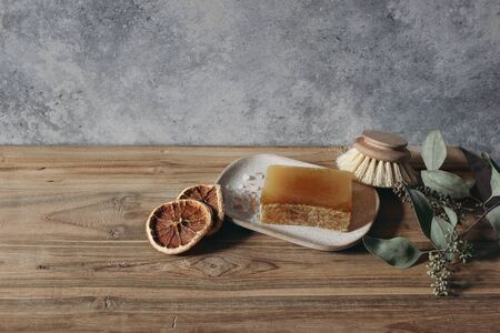 Still life of organic handmade soap bar, wooden brush and dry lemons ruit and eucalyptus on wooden table. Spa, herbal cosmetics concept. Grunge defocused background, skin nourishing.
