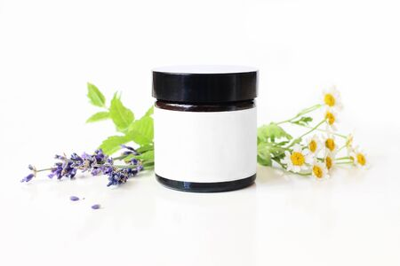 Closeup of dark glass jar with blank paper label. Mint leaves, lavender and feverfew flowers on white table backround. Spa concept. Skin product, moisturizer mockup scene. Cosmetic product packaging.