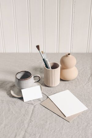Artistic wokspace, still life. Paint brushes, pencils in ceramic holder, vase, cup of coffee and blank paper card mockups on linen tablecloth. Art supplies scene. Creative table background. Top view.