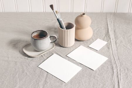 Artistic wokspace, still life. Paint brushes, pencils in ceramic holder, vase, cup of coffee and blank paper card mockups on linen tablecloth. Art supplies scene. Creative table background, top view. Stock Photo