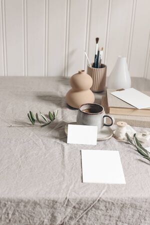 Artistic wokspace, still life. Paint brushes, pencils, olive branches, vase, cup of coffee and blank paper card mockups on linen tablecloth. Art supplies scene. Creative table background, vertical.